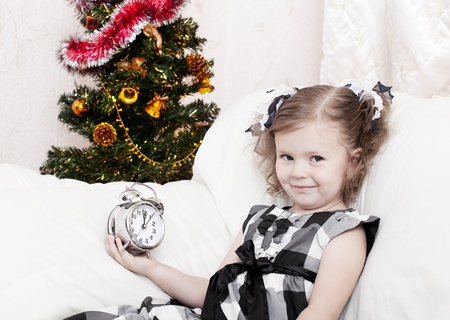 little girl looks at an alarm clock in expectation of Christmas approach photo