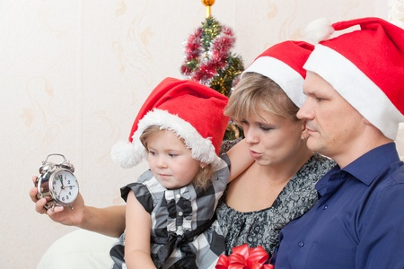 Family with a small daughter in expectation of Christmas photo
