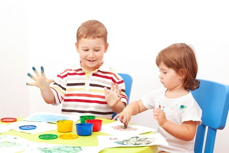 brother and the sister draw finger-type paints Stock Photo
