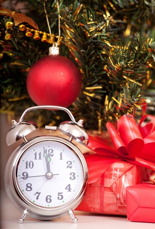 Soon new year! Hours and a gift stand under a fir-tree photo