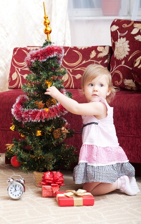 little girl at a Christmas fir-tree. photo