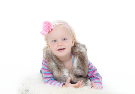 small happy girl in a fur vest on a white background. Studio shooting Stock Photo - 11195184