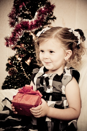 baby christmas: little girl at a Christmas fir-tree. Stock Photo