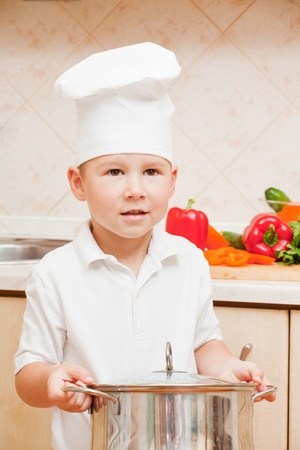 little boy on kitchen helps to make a dinner photo