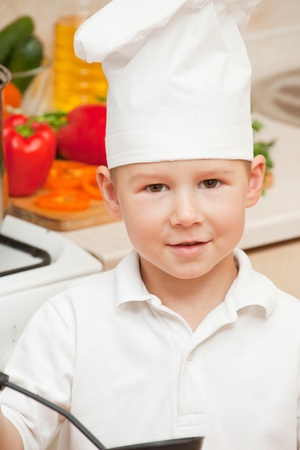 little boy on kitchen helps to make a dinner Stock Photo - 11353612