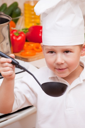 helps: little boy on kitchen helps to make a dinner Stock Photo