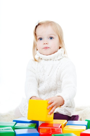 Baby girl plays with toy blocks over white background Stock Photo - 11353527