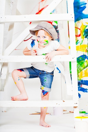 girl in a white T-shirt and a cap bedaubed with bright paints photo