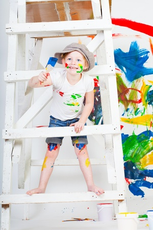 girl in a white T-shirt and a cap bedaubed with bright paints Stock Photo - 11353500