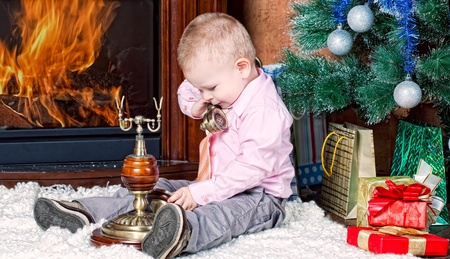 little boy in a room with a fireplace sits at a Christmas fur-tree and calls by phone photo