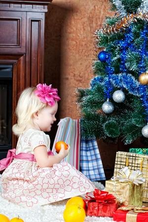 little girl at a Christmas fir-tree photo