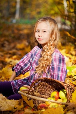 beautiful little girl on walk in autumn park photo