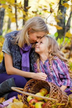 eight year old: Happy mum and the daughter play autumn park on the fallen down foliage Stock Photo