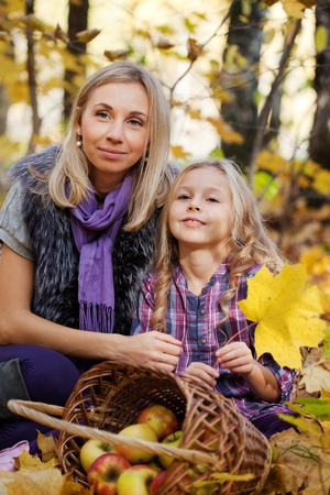 Happy mum and the daughter play autumn park on the fallen down foliage Stock Photo - 11693355