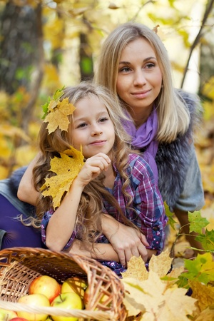 Happy mum and the daughter play autumn park on the fallen down foliage Stock Photo - 11693384