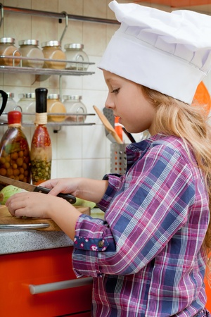 girl in a cook cap helps to make a dinner. Stock Photo - 11693365