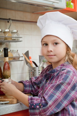 helps: girl in a cook cap helps to make a dinner. Stock Photo