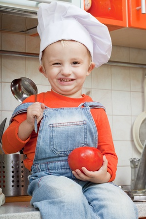 amusing kid in a cook cap on kitchen photo