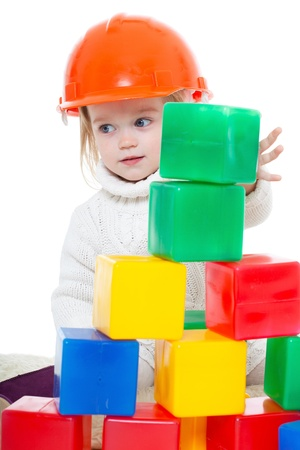 Baby girl plays with toy blocks over white background photo