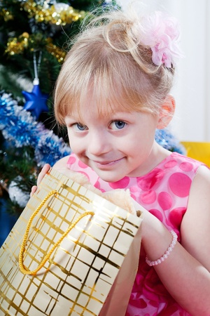 little girl at a Christmas fir-tree photo