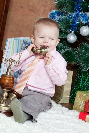 little boy in a room sits at a Christmas fur-tree and calls by phone Stock Photo