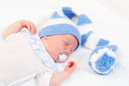 babys dummies: newborn baby (at the age of 7 days) sleeps in a knitted striped hat