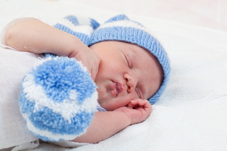 newborn baby (at the age of 7 days) sleeps in a knitted striped hat photo