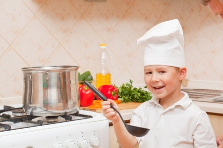 little boy on kitchen helps to make a dinner Stock Photo - 12097902