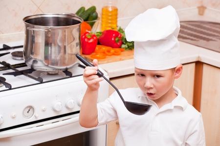 little boy on kitchen helps to make a dinner photo