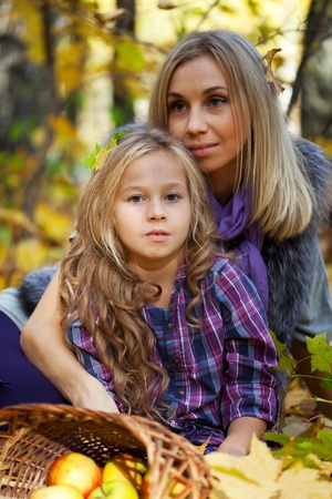 Happy mum and the daughter play autumn park on the fallen down foliage photo