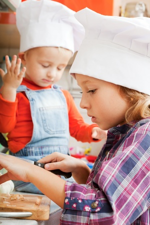 girl in a cook cap helps to make a dinner. photo