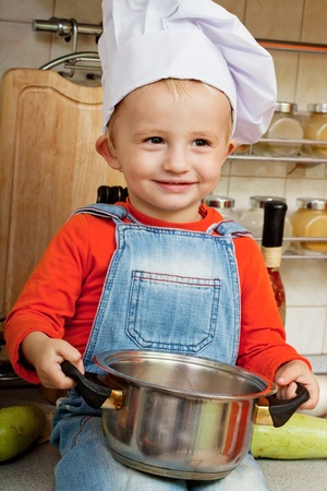 little boy on kitchen helps to make a dinner Stock Photo - 12081473