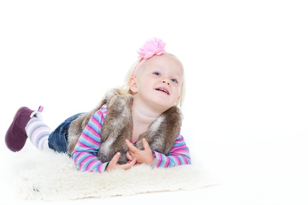 1 2 years: Little blonde girl lying on a sheepskin shoes Stock Photo