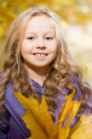 beautiful little girl on walk in autumn park photo