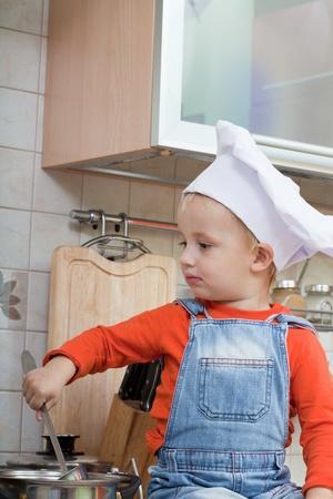 amusing kid in a chef cap on kitchen photo