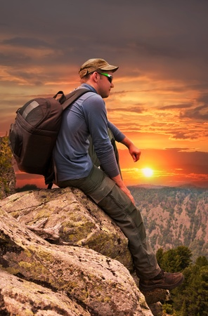 man -  tourist sits on a rock and admires a sunset photo
