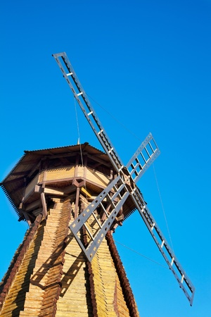 Old wooden mill against the blue sky photo