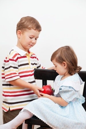 boy gives the little girl a toy photo