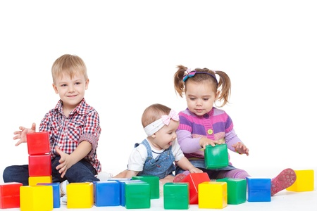 Small children sit on a floor and play with multi-coloured cubes