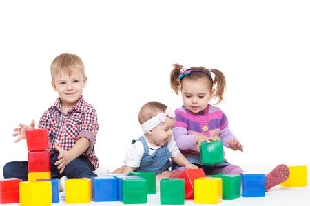 divertirsi: I bambini piccoli seduti su un pavimento e giocare con multi-cubi colorati