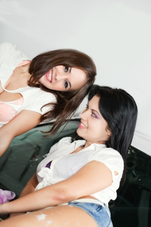 Two girlfriends caress each other in a soapsuds on a bumper of the car photo