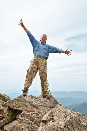 subjugation: Happy mature the man costs at top of mountain, having stretched hands in sides