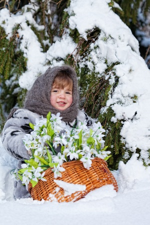 little girl in a winter wood with the big basket of snowdrops photo