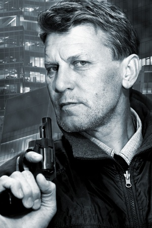 character assassination: Portrait of the serious unshaven man with pistol.