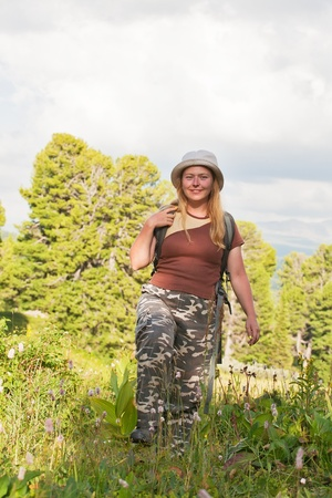 lay forward: happy girl-tourist with a backpack and in a hat goes forward Stock Photo