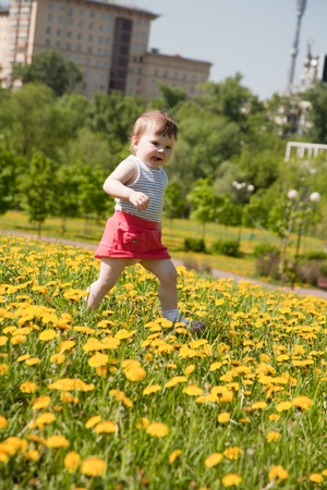 little girl runs on a meadow with dandelions 스톡 콘텐츠