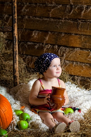 mow: little girl sits on a mow with a jug of milk in hands