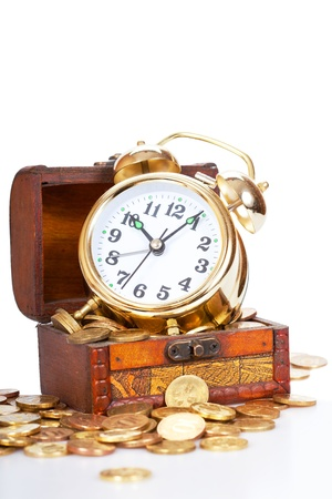Gold alarm clock lay on money in a wooden chest