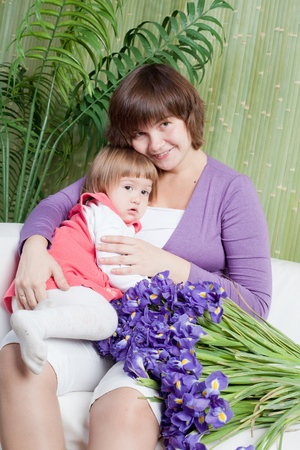 potbelly: little girl gives flowers to pregnant mum Stock Photo
