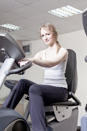 salle de sport: jeune fille dans une salle de sport sur une velosimulator